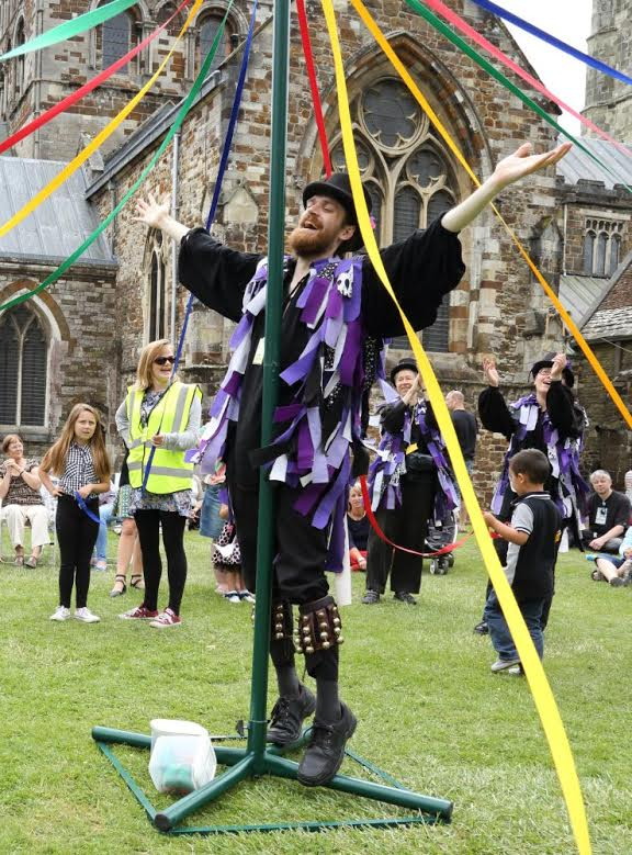 A member of Anonymous Morris is standing at the centre of a maypole dance to stabilise the central pole. We can clearly see his kit as is described by the rest of this article - black hat, shirt, trousers and shoes plus a rag jacket with black, white and purple tatters. Around him we can see children and parents taking part in a maypole dance.